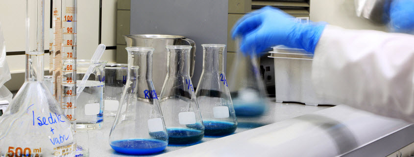 Interior view of a lab, showing the arm of a person in a lab coat and latex gloves lifting a beaker with blue liquid inside