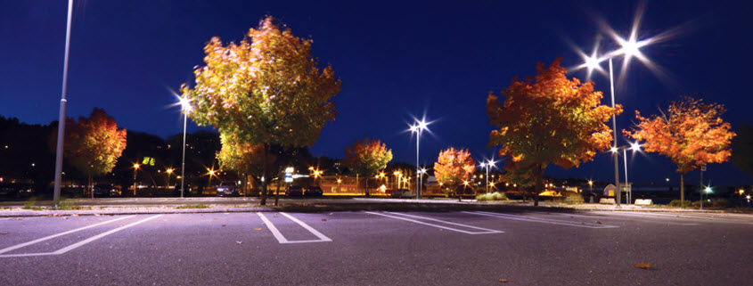 Night time view of a parking lot illuminated with LED street lamps and LED spotlights